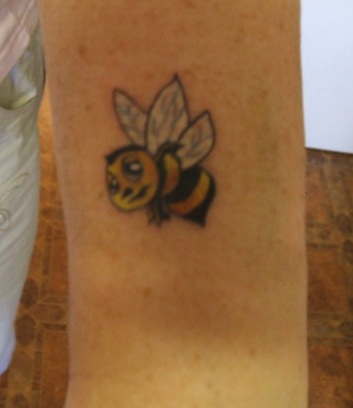 Feminine bumble bee tattoo design on wrist.