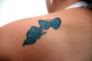 A pair of blue flying butterflies tattoo on left shoulder blade.