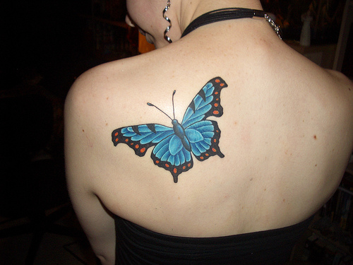 Women with flying blue butterfly tattoo standing in the library.
