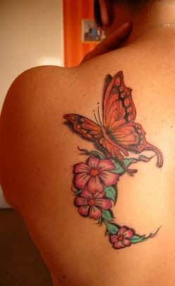 An elegant butterfly with beautiful flowers tattoo on left shoulder blade.