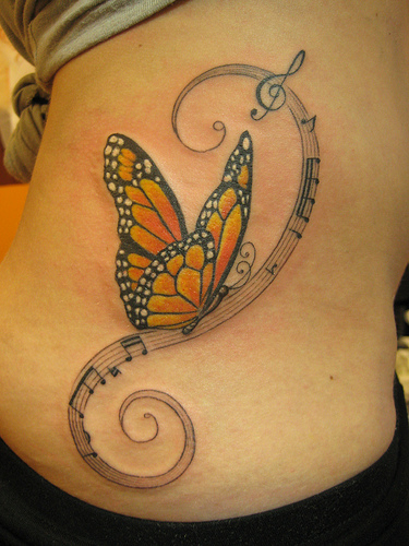 This girl has tattooed a butterfly and musical symbol tattoos on her site.
