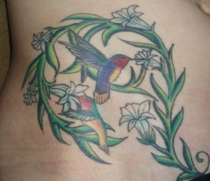 A little flying hummingbird with flowers tattoo on hip.