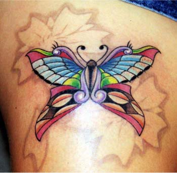 Colorful butterfly with flower tattoo design on thigh.