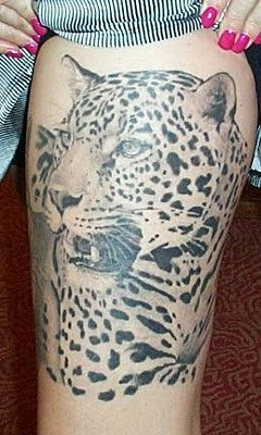 A strength leopard tattoo on girl's thigh.